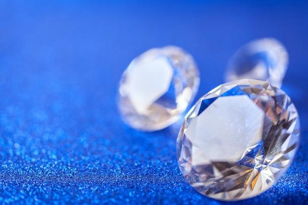 Gros diamants chers posés sur fond de paillettes bleues étincelantes, macro. gros gros plan brillant