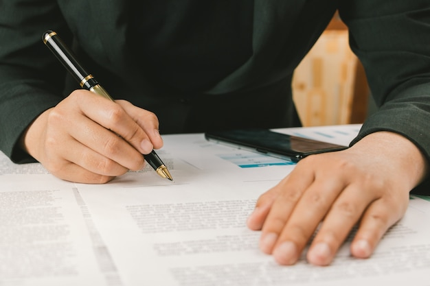 Gros document de termes et conditions de signature de femme d'affaires sur l'espace de travail, signature
