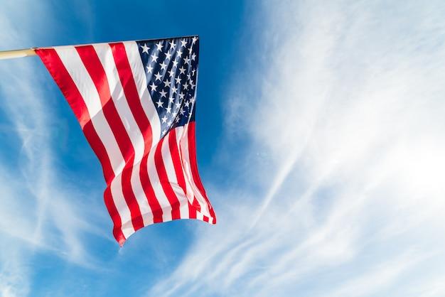 Gros drapeau des états-unis d'amérique sur le fond de ciel bleu. jour de l'indépendance des etats-unis