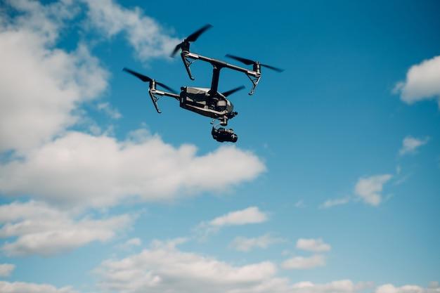 Gros drone quadricoptère contre le vol aérien et le tournage du ciel bleu.