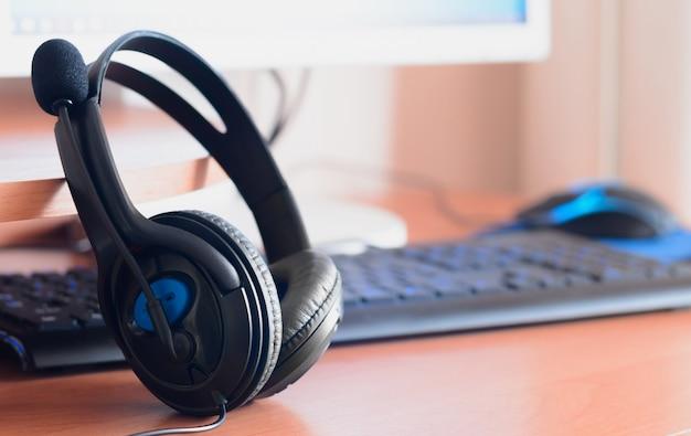 De gros écouteurs noirs se trouvent sur le bureau en bois du concepteur sonore