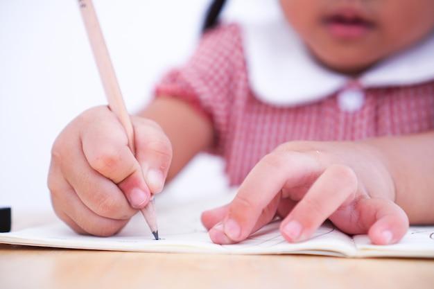 Gros enfant apprenant à écrire sur du papier.