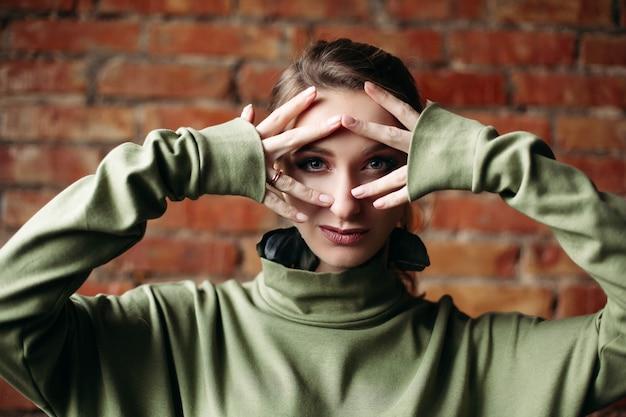 Gros fille vêtue d'une robe kaki touchant le visage par les doigts, posant contre le mur de briques.