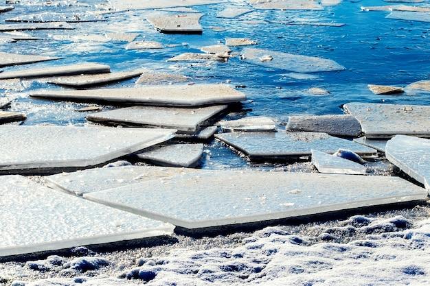 De gros fragments de glace sur la rive de la rivière par temps ensoleillé