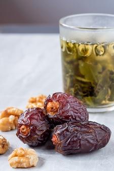 Les gros fruits dattes (medjool) avec noix et thé dans un verre sur un sol en marbre.