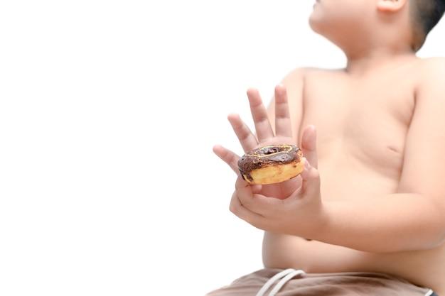 Gros garçon obèse refuse de manger des beignets isolés