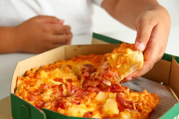 Le gros garçon ramasse une pizza dans le plateau pour le manger.