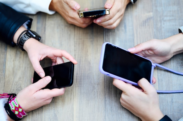 Gros groupe de filles européennes tenant un smartphone ou un téléphone portable avec écran noir. concept de travail et de marketing indépendant de style de vie