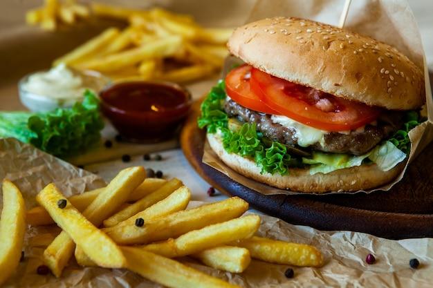 Gros hamburger savoureux sur une table en bois et frites. délicieux burger avec du fromage de tomate de boeuf et de la laitue