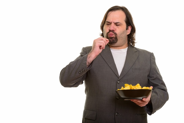 Gros homme d'affaires caucasien mangeant délicieusement bol de chips isolated on white