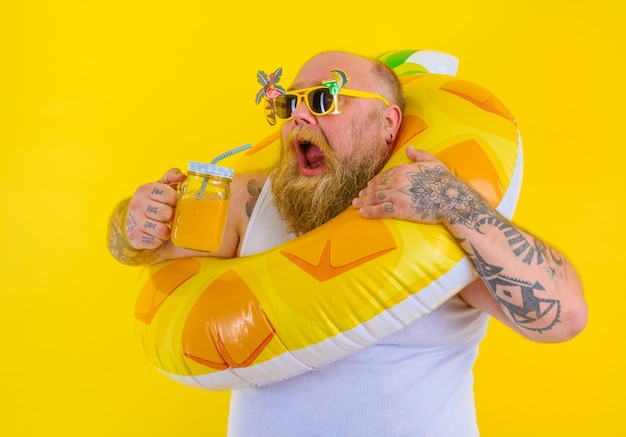 Un gros homme affamé avec une perruque dans la tête est prêt à nager avec une bouée de sauvetage en forme de beignet