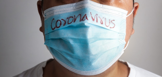 Un gros homme asiatique portant un masque bleu écrit le mot coronavirus. concept de prévention du covid-19 l'espacement social empêche la propagation du virus, en prenant soin des personnes obèses.