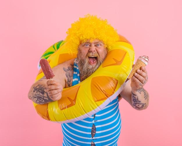 Gros homme avec barbe et perruque mange un popsicle et une glace