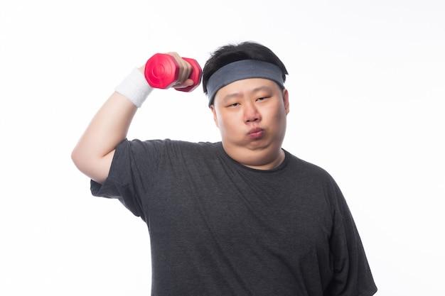 Gros homme drôle asiatique dans des tenues de sport exerçant avec haltère