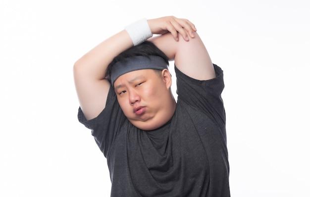 Gros homme drôle asiatique dans des tenues de sport faire des étirements avant l'entraînement et à la recherche d'appareil photo isolé sur fond blanc