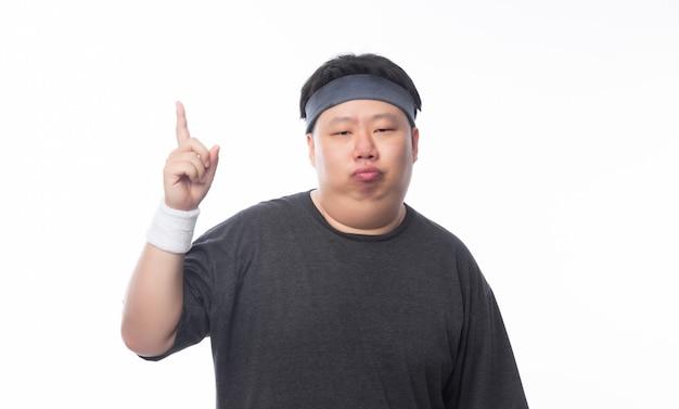 Gros homme drôle asiatique en tenue de sport pointant