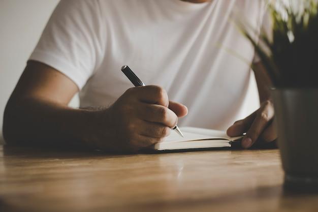 Gros homme écrivant la mémoire sur la table dans un style vintage