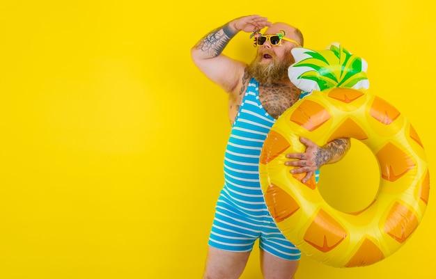 Un gros homme étonné avec une perruque dans la tête est prêt à nager avec une bouée de sauvetage en forme de beignet