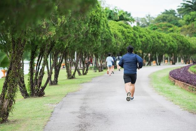 Gros homme, faire du jogging au parc public