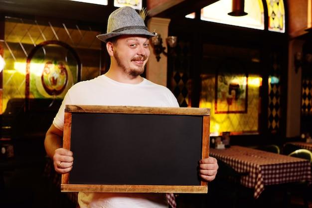Un gros homme gai avec un chapeau bavarois et une plume lors de la célébration de la fête de la bière tient un panneau ou un tableau noir dans ses mains