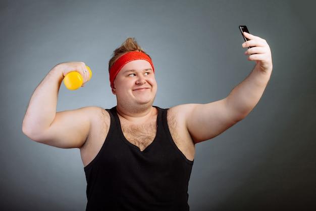 Gros homme avec gros ventre, tenant des haltères, faisant selfie sur mur gris
