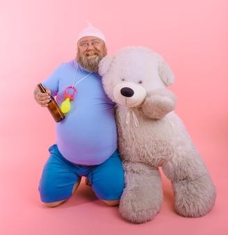 Un gros homme heureux agit comme un bébé heureux mais boit de la bière