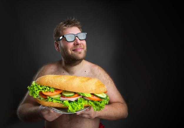 Gros homme heureux dans des verres avec sandwich sur fond noir