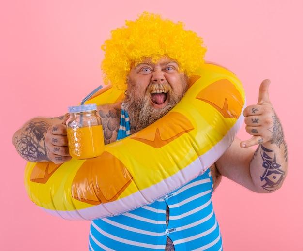 Un gros homme heureux avec une perruque dans la tête est prêt à nager avec une bouée de sauvetage en forme de beignet
