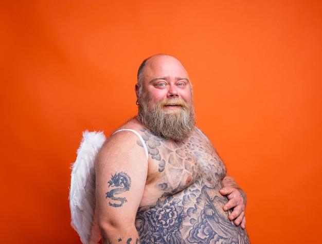 Un gros homme heureux avec des tatouages de barbe et des ailes agit comme un ange