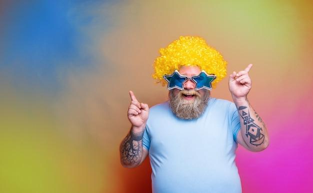 Gros homme heureux avec des tatouages de barbe et des lunettes de soleil danse de la musique dans une discothèque