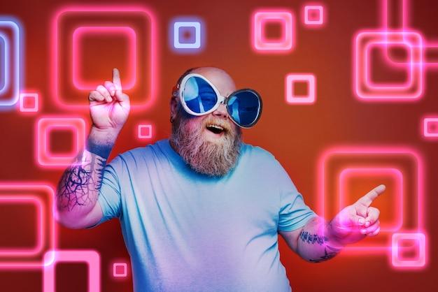 Gros homme heureux avec des tatouages de barbe et des lunettes de soleil danse de la musique