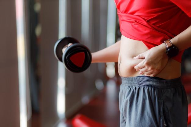 Gros homme, main d'homme obèse tenant la graisse du ventre excessive isolée sur fond de gym