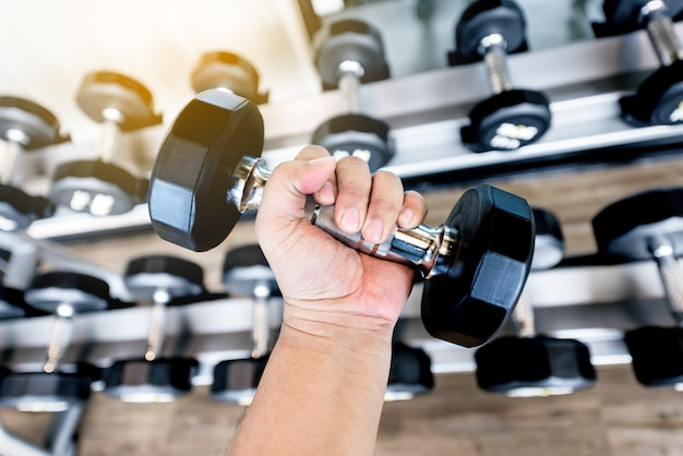 Gros homme main tenant des haltères en métal noir dans la salle de gym