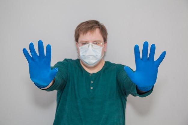 Gros homme en masque et gants demande d'arrêter