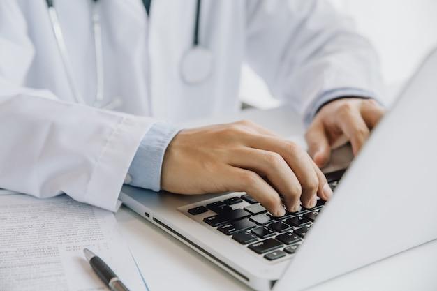Gros homme médecin tapant sur un ordinateur portable assis à la table. le personnel médical