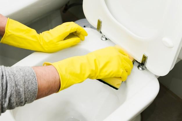 Gros homme nettoyant les toilettes avec une éponge
