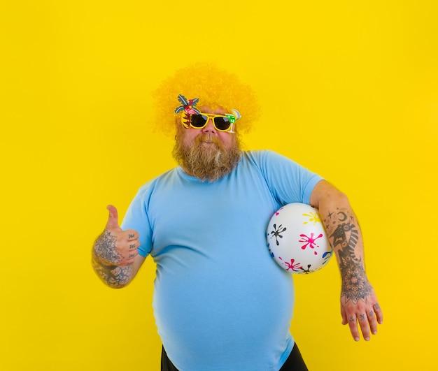 Gros homme avec perruque dans la tête et lunettes de soleil s'amuser avec une balle
