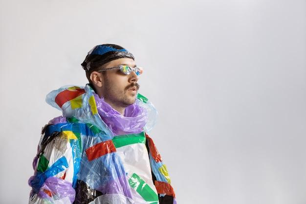 Gros homme portant du plastique sur un mur blanc. modèle masculin dans des vêtements faits d'ordures. mode, style, recyclage, concept écologique et environnemental. trop de pollution, on en mange et on en prend.