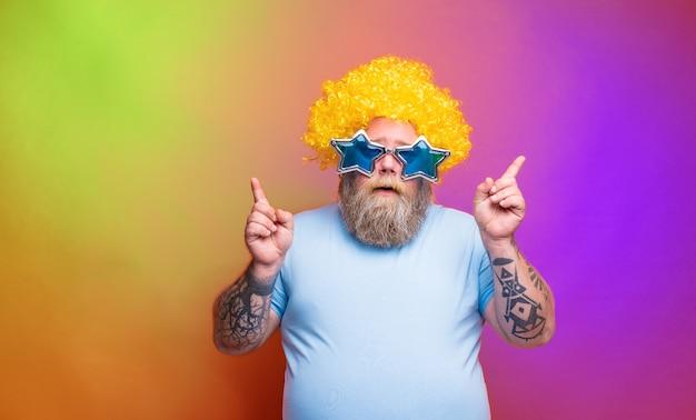 Gros homme réfléchi avec des tatouages de barbe et des lunettes de soleil danse de la musique dans une discothèque