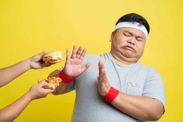 Gros homme refuse de manger de la pizza et des hamburgers