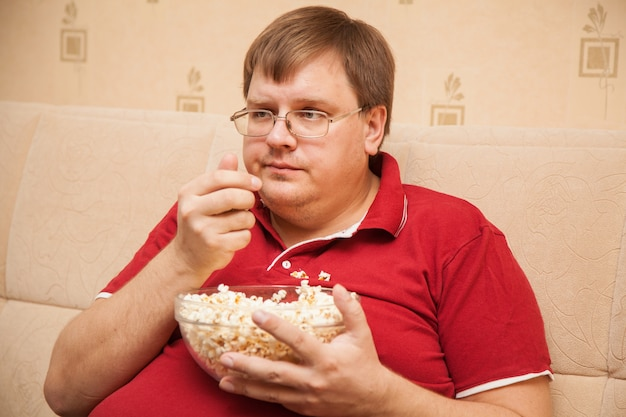 Gros homme regardant la télévision manger du pop-corn
