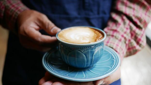 Gros homme servant du café chaud au café.