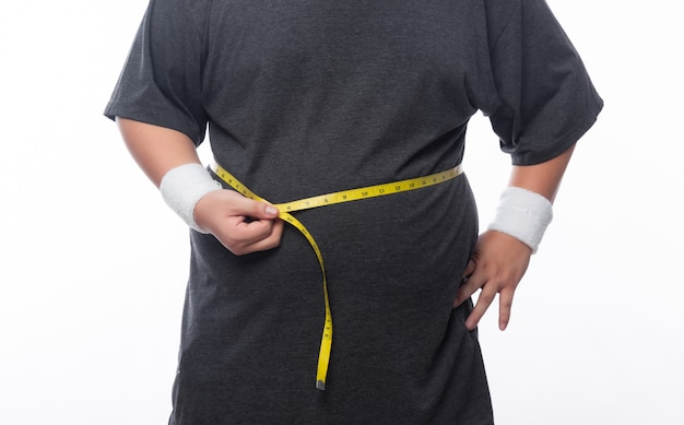Gros homme tenant un ruban de mesure pour vérifier son corps isolé sur fond blanc
