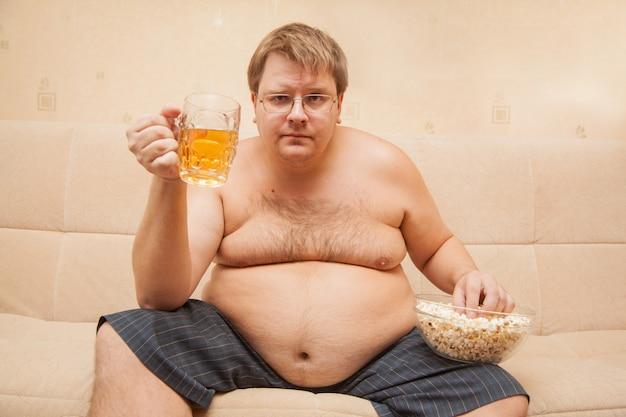 Gros homme avec ventre de bière devant la télé mange du pop-corn et boit de la bière