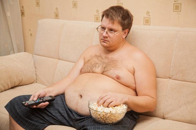 Gros homme avec ventre de bière devant la télé, manger du pop-corn