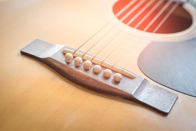 Gros morceau de guitare acoustique, détail des cordes de guitare et des accords de mesure.