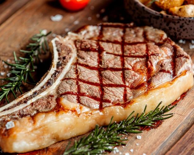Un gros morceau de steak avec des feuilles d'estragon
