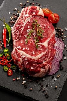 Un gros morceau de viande sur l'os se trouve sur une planche de bois avec des épices et des herbes fraîches