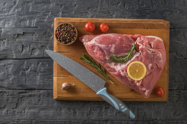 Un gros morceau de viande de porc, un couteau, des tomates et de l'ail sur une planche à découper. ingrédients pour la cuisson des plats de viande. la vue depuis le sommet.