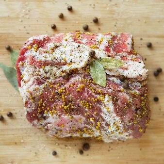 Un gros morceau de viande de porc grasse marinée à la moutarde, au poivre et à divers condiments